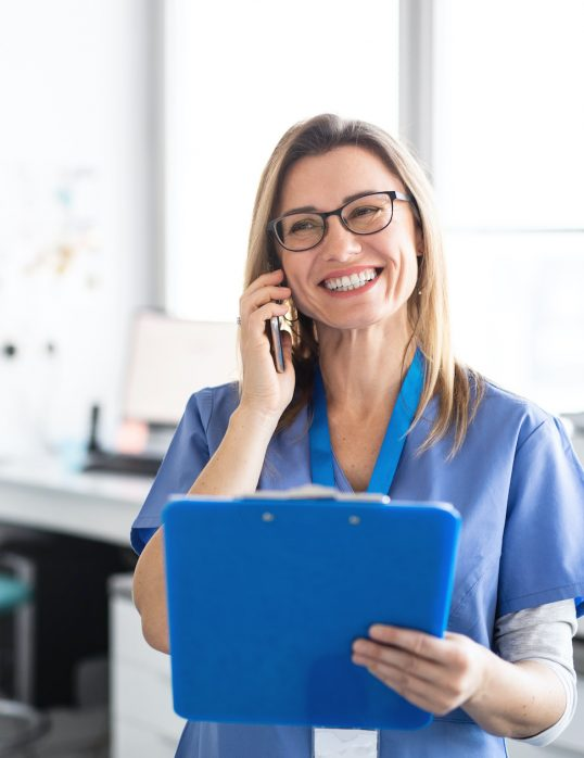 A portrait of cheerful dental assistant in modern dental surgery, using smartphone.